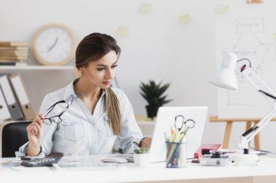 mujer-negocios-sosteniendo-sus-gafas-trabajando-computadora-portatil_23-2148352752